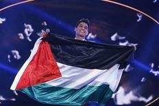 "Palestinian singer Mohammed Assaf holds the Palestinian flag, as he stands on stage after being announced winner during the Season 2 finale of ""Arab Idol"" in Zouk Mosbeh area, north of Beirut June 22, 2013. REUTERS/Mohammed Azakir"