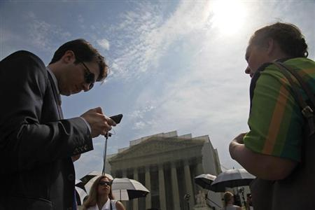 Court watchers and reporters wait outside the U.S. Supreme Court building for news of their rulings in cases heard earlier this year in Washington, June 24, 2013. REUTERS/Jonathan Ernst