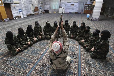 Abu al-Taib, the leader of Ahbab Al-Mustafa Battalion, demonstrates to female members as he holds a gun during a military training in a mosque in the Seif El Dawla neighbourhood in Aleppo June 24, 2013. REUTERS-Muzaffar Salman