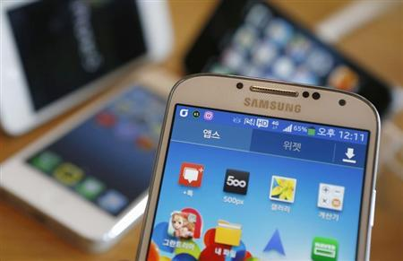 A Samsung Electronics' Galaxy S4 (front) and Apple's iPhone 5 smartphones are seen in this picture illustration taken in Seoul May 13, 2013. REUTERS/Kim Hong-Ji
