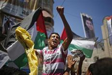 """Pessoas acenam bandeiras palestinas enquanto aguardam chegada do vencedor do programa """"Arab Idol"""" Mohammed Assaf perto de sua casa, no sul da Faixa de Gaza. 25/06/2013 REUTERS/Mohammed Salem"""