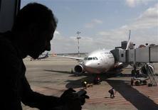 """Пассажир с телефоном в транзитной зоне Шереметьево на фоне самолета Аэрофлота, готовящегося вылететь в Гавану 24 июня 2013 года. Бывший сотрудник ЦРУ Эдвард Сноуден, вопреки ожиданиям, этим рейсом не улетел, и по прежнему находится в транзитной зоне московского аэропорта, сказал президент РФ Владимир Путин во вторник вечером, и пожелал, чтобы """"свободный человек"""" скорее нашел себе новую родину, а его транзит через Шереметьево не повредил отношениям Москвы с Вашингтоном. REUTERS/Maxim Shemetov"""