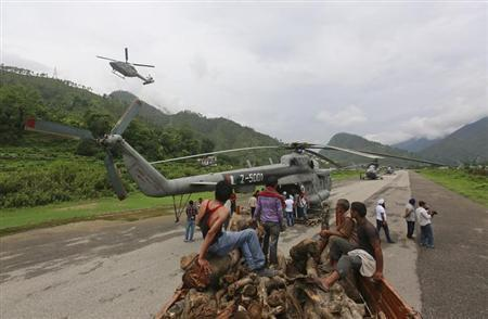 Volunteers wait to unload wood from a truck to be used for mass cremation at Kedarnath at an airport in Gauchar in Uttarakhand June 25, 2013. REUTERS/Danish Siddiqui