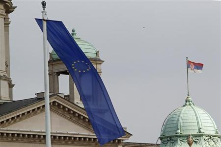 A Serbian flag (R) and a EU flag are seen in front of Serbia's Parliament building in Belgrade March 2, 2012. REUTERS/Ivan Milutinovic