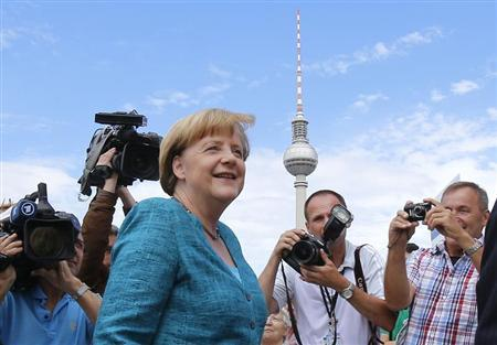 German Chancellor and leader of the Christian Democratic Union (CDU) Angela Merkel (C) arrives for a party meeting with the Christian Social Union (CSU) in Berlin June 23, 2013. The building in the background is the television tower. REUTERS/Tobias Schwarz