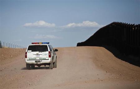 U.S. Border Patrol surveys the border fence near rancher John Ladd's property adjacent to the Arizona-Mexico border near Naco, Arizona, March 29, 2013. REUTERS/Samantha Sais
