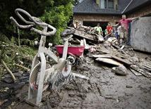 A mud-covered exercise bike sits outside a home as residents clean up after floods in Calgary, Alberta June 25, 2013. REUTERS/Andy Clark