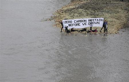 Environmental activists hold a banner which reads ''Zero carbon Britain before we drown'' on the bank of the Thames across from the Houses of Parliament in London July 16, 2011. REUTERS/Suzanne Plunkett/Files