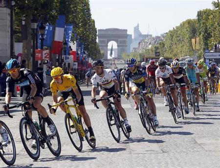 Sky Procycling rider and leader's yellow jersey Bradley Wiggins of Britain (2ndL) cycles on the Champs Elysees during the final 20th stage of the 99th Tour de France cycling race between Rambouillet and Paris, July 22, 2012. REUTERS/Bogdan Cristel