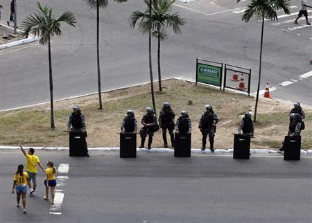 Soccer fans walk past members of a Brazilian special anti-riot unit at a security checkpoint outside the stadium before the Confederations Cup soccer match between Brazil and Italy in Salvador June 22, 2013. REUTERS/Paulo Whitaker