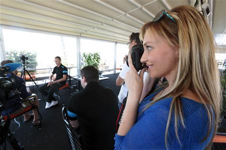 Michelle Cound (R), girlfriend of British cyclist Chris Froome (rear L) of Team Sky, takes a photo during his interview with the media in Nice in this June 18, 2013 file photo. REUTERS/Eric Gaillard/Files