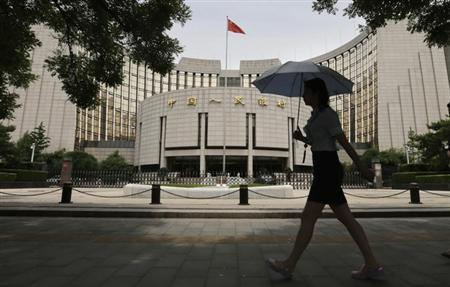 A woman walks past the headquarters of the People's Bank of China (PBOC), the central bank, in Beijing, June 21, 2013. REUTERS/Jason Lee