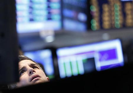 A trader looks up at a screen on the floor at the New York Stock Exchange, June 25, 2013. REUTERS/Brendan McDermid