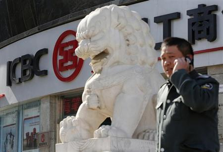 A man uses a mobile phone in front of a branch of the Industrial and Commercial Bank of China Ltd (ICBC) in Beijing March 27, 2013. REUTERS/Kim Kyung-Hoon