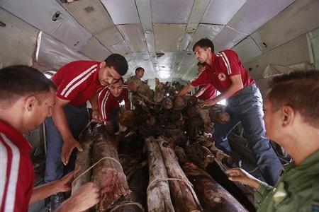 Soldiers and volunteers load wood on an Indian Air Force helicopter to be used for mass cremation at Kedarnath at an airport in Gauchar in Uttarakhand June 25, 2013. REUTERS/Danish Siddiqui