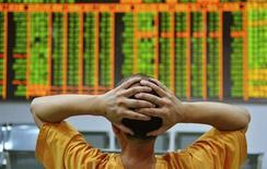 Инвестор сидит перед экраном с рыночной информацией в брокерской конторе в городе Ханчжоу провинции Чжэцзян 24 июня 2013 года. Стоимость краткосрочных ресурсов на денежном рынке Китая снижается четвертый день подряд в среду, после того как центробанк сообщил на прошлой неделе, что недооценил кредитный кризис и оказал помощь ряду институтов. REUTERS/China Daily