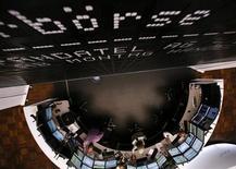 Трейдеры сидят под экраном с графиком индекса DAX на фондовой бирже во Франкфурте-на-Майне 21 июня 2013 года. Европейские рынки акций открылись снижением в среду, несмотря на неожиданно высокие макроэкономические показатели США. REUTERS/Ralph Orlowski
