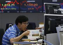 Валютный дилер обедает в дилерской комнате банка в Сеуле 21 июня 2013 года. Азиатские фондовые рынки завершили торги среды разнонаправленно на фоне опасений за банковский сектор Китая и локальных факторов. REUTERS/Kim Hong-Ji
