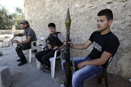 Free Syrian Army fighters carry their weapons as they sit near the frontline in the Al-Sakhour neighborhood of Aleppo, June 21, 2013. REUTERS/Muzaffar Salman
