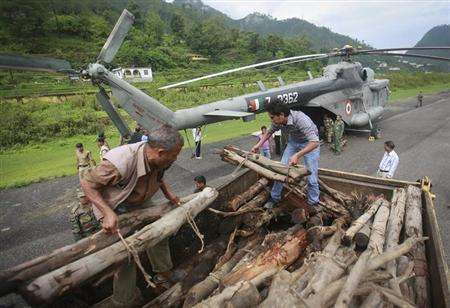 Volunteers unload wood from a truck to be used for mass cremation at Kedarnath at an airport in Gauchar in Uttarakhand June 25, 2013. REUTERS/Danish Siddiqui