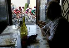 A man in a cafe looks out of the window at a pack of riders making their way through the 230-km (143-mile) sixth stage of the Tour de France cycling race between Nevers and Lyon in this July 11, 2003 file photo. REUTERS/Vincent Kessler/Files