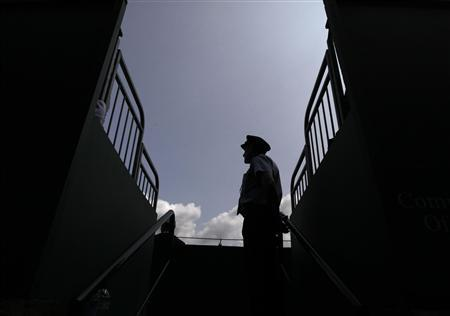 A security guard stands at the top of a flight of steps on court three at the Wimbledon Tennis Championships, in London June 25, 2013. REUTERS/Stefan Wermuth