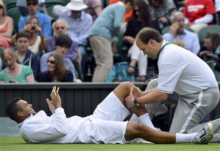 Jo-Wilfried Tsonga of France receives treatment during his men's singles tennis match against Ernests Gulbis of Latvia at the Wimbledon Tennis Championships, in London June 26, 2013. REUTERS/Toby Melville