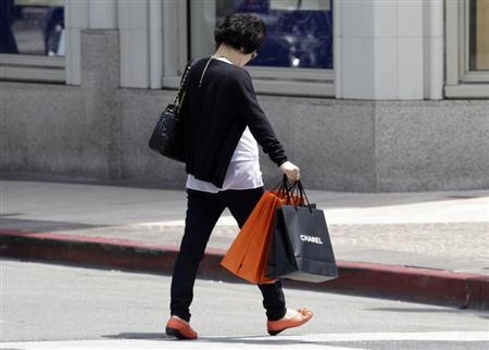 A woman carrying a Chanel shopping bag walks on Rodeo Drive in Beverly Hills, California, May 21, 2013. REUTERS/Fred Prouser