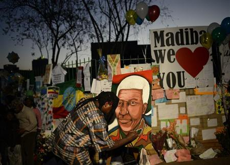 A man paints a portrait of ailing former South African President Nelson Mandela outside the Medi-Clinic Heart Hospital where he is being treated in Pretoria June 26, 2013. REUTERS/Dylan Martinez