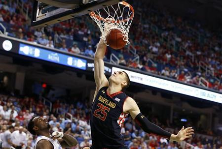 Maryland Terrapins center Alex Len (R) dunks the ball over North Carolina Tar Heels guard P.J. Hairston (L) during the first half of their ACC Championship college basketball game in Greensboro, North Carolina March 16, 2013. REUTERS/Chris Keane