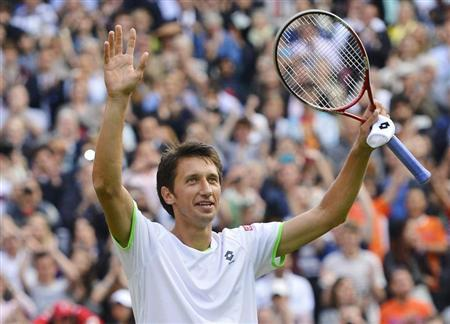Sergiy Stakhovsky of Ukraine reacts after defeating Roger Federer of Switzerland in their men's singles tennis match at the Wimbledon Tennis Championships, in London June 26, 2013. REUTERS/Toby Melville