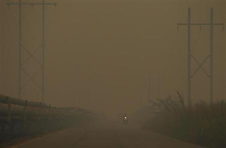 Motorists drive through the haze at Bangko Pusako district in Rokan Hilir, on Indonesia's Riau province, June 24, 2013. REUTERS/Beawiharta