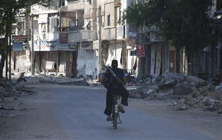 A Free Syrian Army fighter rides his bicycle in Daraya town near Damascus June 20, 2013. REUTERS/Mohamed Demashki