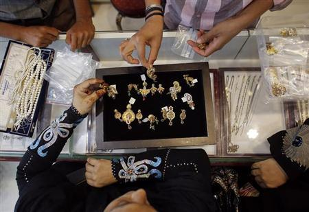 A customer looks at a gold pendent inside a jewellery showroom in Mumbai June 4, 2013. REUTERS/Danish Siddiqui