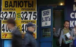 Люди проходят мимо вывески обменного пункта в Москве 31 мая 2012 года. Рубль подорожал к бивалютной корзине и её компонентам, отыгрывая снижение спроса на безопасные активы и рост в цене рискованных и сырьевых инструментов в ответ на ожидания сохранения монетарных стимулов ФРС после слабой американской статистики; поддержку оказывали и продажи экспортной выручки под уплату налога на прибыль, а также валютные интервенции Центробанка. REUTERS/Maxim Shemetov
