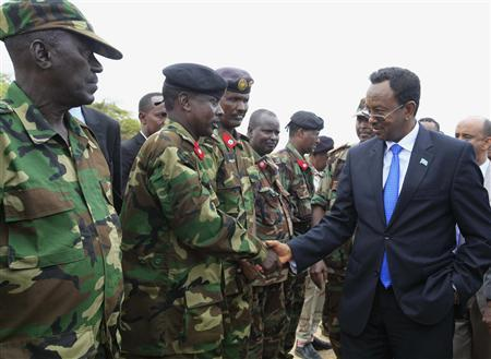Somalia's Prime Minister Abdi Farah Shirdon Saaid (R) meets senior military officials upon arrival at the passing out parade of newly trained soldiers in Mogadishu June 24, 2013. REUTERS/Feisal Omar