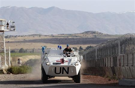 United Nations (U.N.) peacekeeping soldiers from Austria drive past an observation tower near the Quneitra border crossing between Israel and Syria, on Israeli-occupied Golan Heights June 12, 2013. REUTERS/Ammar Awad