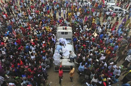 Relatives of garment workers who were working in the Rana Plaza building when it collapsed, gather around a truck carrying dead bodies, in Savar, 30 km (19 miles) outside Dhaka April 27, 2013. REUTERS/Stringer