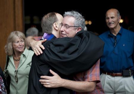 Joe Silverman (R) hugs his partner of 27 years, Rev. Paul Mowry, following Sunday service at Sausalito Presbyterian Church in Sausalito, California June 23, 2013. REUTERS/Noah Berger