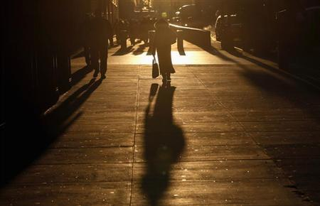 Commuters walk down West 42nd Street as the sun rises in New York City January 24, 2013. REUTERS/Mike Segar