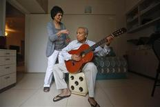 Aruna Gokhale (L), 81, watches as her husband Vidyadhar Gokhale, 84, plays guitar in their flat at the Athashri retirement village in Baner, on the outskirts of the western Indian city of Pune, June 18, 2013. REUTERS/Danish Siddiqui