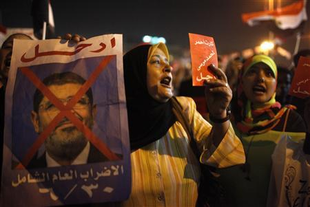A protester holds a crossed out picture of President Mohamed Mursi while chanting anti-Mursi and anti-Muslim Brotherhood slogans as they wait in Tahrir square ahead of Mursi's public address, in Cairo June 26, 2013. REUTERS/Asmaa Waguih