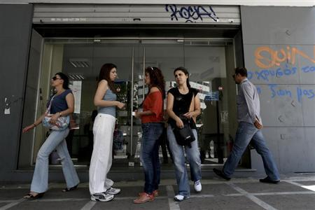 People enter and leave a Greek Manpower Employment Organisation office in Athens June 6, 2013. REUTERS/John Kolesidis