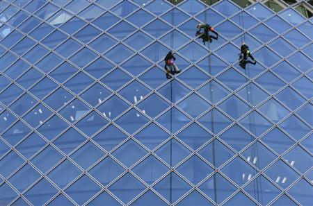 Workers clean windows of an office building in Tokyo's business district February 20, 2013. REUTERS/Toru Hanai