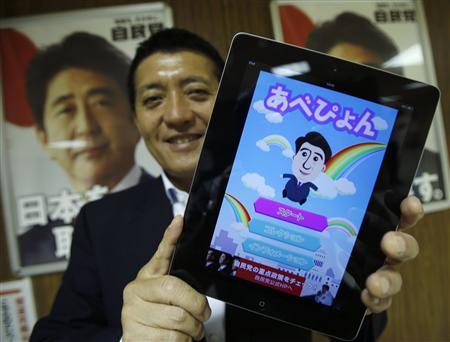 Takuya Hirai, Director of Internet Media Division of Japan's ruling Liberal Democratic Party (LDP), poses with an iPad displaying ''Abe Pyon'', LDP's official game application programme featuring Shinzo Abe, Japan's Prime minister and LDP's leader, at the LDP headquarters in Tokyo June 27, 2013. REUTERS/Toru Hanai