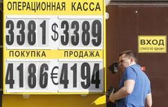 Мужчина заходит в пункт обмена валют в Москве 1 июня 2012 года. Рубль растет к бивалютной корзине благодаря поддержке экспортеров в последний день уплаты налога на прибыль. REUTERS/Denis Sinyakov