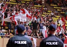 """Полицейские стоят у трибуны с болельщиками """"Монако"""" во время матча Лиги 2 между """"Монако"""" и """"Каном"""" в Монте-Карло 4 мая 2013 года. Руководство французской лиги (LFP) наказало """"Монако"""" лишением двух очков в новом сезоне за поведение болельщиков вернувшегося в элитный дивизион клуба, сообщила в четверг LFP. REUTERS/Eric Gaillard"""