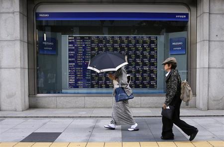 A woman wearing a kimono holds an umbrella as she walks past an electronic stock quotation board outside a brokerage in Tokyo May 23, 2013. REUTERS/Toru Hanai