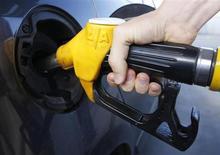 Клиент АЗС заправляет автомобиль в Труштершеме 26 августа 2012 года. Цены на нефть Brent повышаются и завершат июнь ростом впервые за пять месяцев благодаря заверениям чиновников ФРС, что центробанк не спешит сокращать программу скупки облигаций. REUTERS/Vincent Kessler