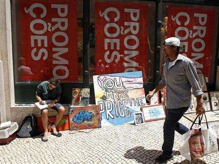 A man walks past a painter selling his work in front of a shop announcing promotions during the general strike in Lisbon June 27, 2013. REUTERS/Jose Manuel Ribeiro